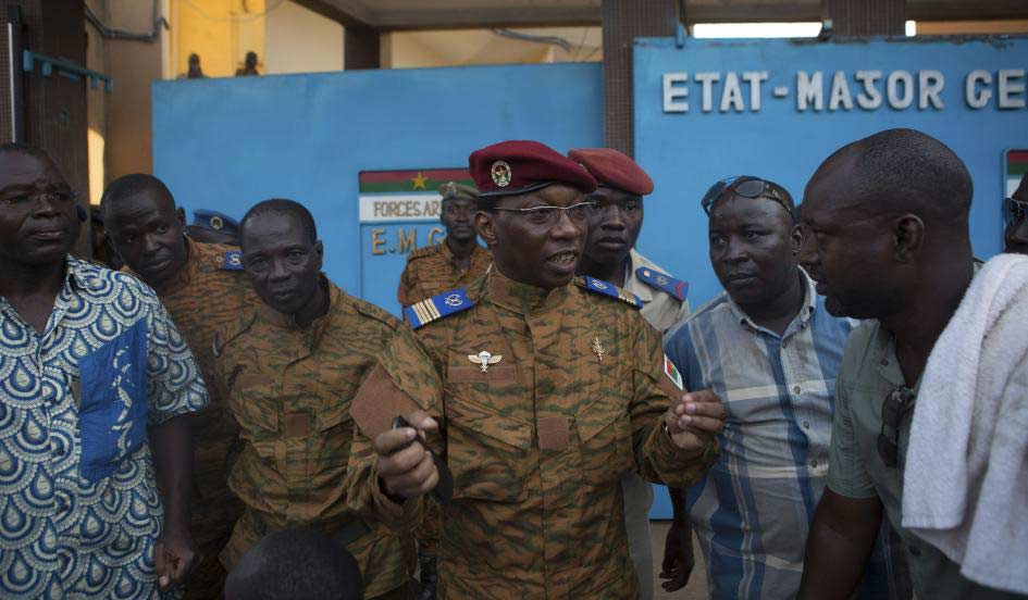 An army spokesman speaks to anti-government protesters outside military headquarters in Ouagadougou, capital of Burkina Faso, October 30, 2014. Burkina Faso's President Blaise Compaore declared a state of emergency on Thursday and pledged to open talks with the opposition, local radio reported, in a bid to defuse protests sparked by his attempt to extend his 27-year rule.  Joe Penney/Reuters