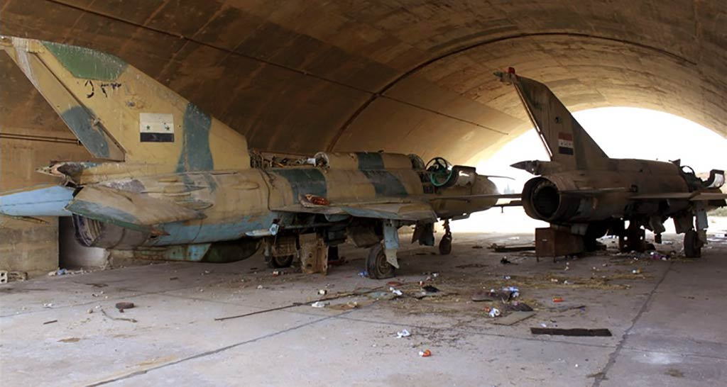 The actual number of MiG-21s found by Daesh at Tabqa AB is much higher than originally assessed. While Google Earth photos indicate presence of about 23 MiG-21s at Tabqa prior to its fall, review of all the videos and photos meanwhile published by extremists (many were subsequently deleted, i.e. accounts blocked) totalled at 1 MiG-21bis, 11 MiG-21MF, 1 MiG-21M and no less but 10 MiG-21UMs – i.e. all the 23 that should have been htere. 14 of these 23 aircraft were meanwhile positivelly identified by their serials. Two of these – the sole MiG-21bis and one of MFs – appear to be in at least 'reasonable' condition: i.e. they were in active service with the Syrian Arab Air Force until relatively recently. This leads to the conclusion that, provided the Daesh finds the people with the necessary know-how (and it should be known they're activelly searching for and recruiting anybody with technical skills), and finds the necessary spares, it might prove capable of overhauling and returning at least these two MiG-21s to service. To make sure: this is no 'theory/speculation', on the contrary. Precisely the above-mentioned example of the 'Islamic Emirate of Afghanistan Air Force', i.e. the 'Taliban Air Force', is a very good example for such 'groups' being able of running 'high-tech' military organizations. Namely – and contrary to what's mentioned in your article on that 'Taliban Air Force' – it did not 'force' or 'use captured pilots and technicians' to fly MiG-21s, Su-20s etc. It was organized and run by personnel that defected from the former Democratic Republic of Afghanistan Air Force, and supported by Pakistani military. And it evolved into a well-organized and combat-effective fighting force (of course, this stood no chance against US air power unleashed against the Taliban in late 2001). Surely enough, most of those joining the Daesh have no clue how to maintain or operate something like a MiG-21: it's not only that majority are coming from countries that never operate