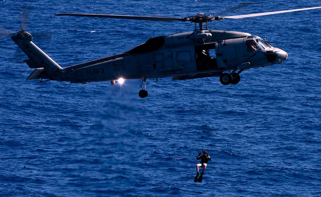 Search and rescue swimmer is deployed from an USN SH-60F Sea Hawk helicopter. A search and rescue swimmer is deployed from an SH-60F Sea Hawk helicopter assigned to Helicopter Anti-submarine squadron (HS) 15 during an air power demonstration over the Nimitz-class aircraft carrier USS Carl Vinson (CVN 70). Carl Vinson and Carrier Air Wing (CVW) 17 are underway in the U.S. 7th Fleet area of responsibility. (U.S. Navy photo by Mass Communication Specialist 3rd Class Travis K. Mendoza/R  Official U.S. Navy Page / ACIFIC OCEAN,June 3, 2011)
