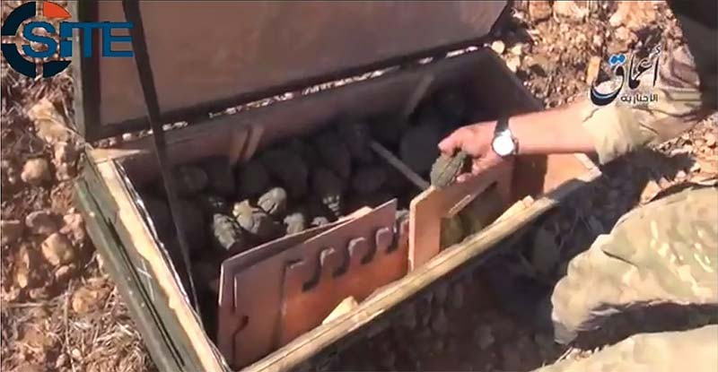 This screen grab, taken from a video released by the SITE Intelligence Group, allegedly depicts an Islamic State fighter looking at hand grenades the U.S. military attempted to airdrop to Kurdish fighters near Kobane, Syria. (Video screen grab)