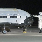 Technicians work on the the first X-37B space plane after a smooth landing on Dec. 3, 2010 at Vandenberg Air Force Base in California. The same X-37B spacecraft launched back into space on Dec. 11, 2012. (Photo by U.S. Air Force)