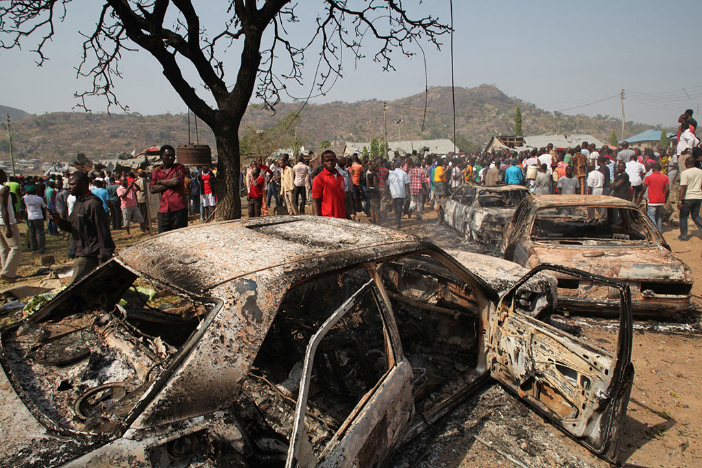 People gather around burnt cars near a Catholic church after a bomb blast in Nigeria's capital, Abuja, on December 25, 2011.